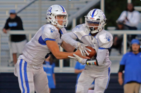 Senior Bo Kite hands the ball off to Senior Miles Ellis in a football game last year at Atlee.